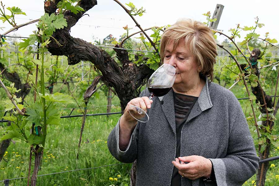 Valentina Cubi tastes a glass of wine inside her vineyard